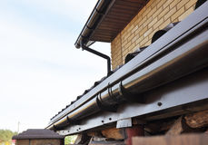 Holder gutter drainage system on the roof. Closeup of problem areas for plastic rain gutter waterproofing. Royalty Free Stock Image