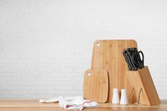 Holder with knives and clean boards on table against white brick wall. Space for text royalty free stock images