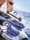 Holder of rope on sailboat. Man pulling handle of spool, macro photo of yacht detail, working on water transport, luxury summer time sport Royalty Free Stock Image