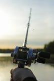 Holdig masculino de la mano un carrete redondo de la pesca Imágenes de archivo libres de regalías