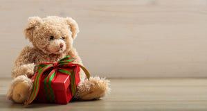 Holdimg плюшевого медвежонка подарок на деревянном поле Стоковые Изображения RF