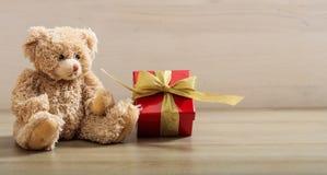 Holdimg плюшевого медвежонка подарок на деревянном поле Стоковое Изображение RF