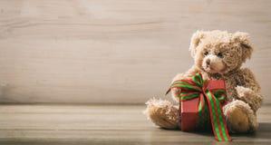 Holdimg del oso de peluche un regalo en un piso de madera fotos de archivo libres de regalías
