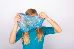 Holdin de jeune fille une boue bleue de scintillement de transparend devant son visage photographie stock
