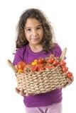 Holdin de la muchacha una cesta de tomates Imagenes de archivo