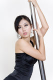 Holding on. A portrait of a beautiful asian girl who is holding on to a pole for support Stock Photo