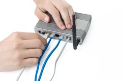 Holding ADSL router and connecting network plug. ADSL router hold by man against white. Connecting network plug stock images