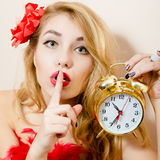 Holding alarm-clock beautiful glamor young blond pinup woman in red dress showing silence sign & looking at camera on white. Glamor young blond pinup woman in Royalty Free Stock Photos