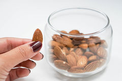 Holding almond. Holding an almond from the transparent bowl Stock Image