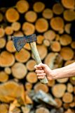 Holding an ax on firewood background Stock Photos