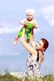 Holding baby girl. A beautiful mother holding her young baby girl high up in the air Stock Photo