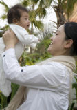 Holding Baby High. A young Chinese mother holds her baby up to the sky in adoration and love Stock Photos