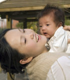 Holding Baby High. A young Chinese mother holds her baby up in adoration and love Stock Photo