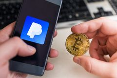 Holding Bitcoin coin with Paypal application royalty free stock images