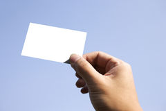 Holding blank business card. In blue sky Royalty Free Stock Images