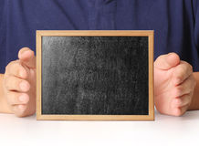 Holding blank chalkboard in hand Stock Photo