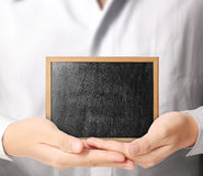 Holding blank chalkboard in  hand Royalty Free Stock Image