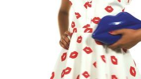 Holding Blue Handbag modelo en forma de los labios Wearing modelo un vestido Pin-Para arriba que presenta en estudio en el fondo  almacen de video