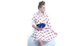 Holding Blue Handbag modelo rubio hermoso en forma de los labios Wearing modelo un vestido Pin-Para arriba que presenta en estudi almacen de metraje de vídeo