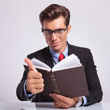 Holding book and thumb up sign Stock Photos