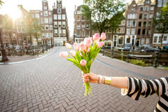 Holding tulips in Amsterdam. Holding a bouquet of pink tulips outdoors on the beautiful buildings background during the morning in Amsterdam city Stock Images