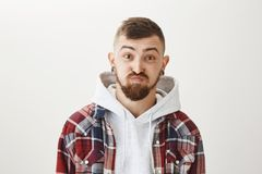 Holding breath, having no words to describe his surprise. Portrait of handsome funny caucasian guy with stylish haircut. And flesh tunnels, lifting eyebrows Stock Photo
