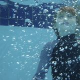 Holding breath underwater. Young boy holding breath underwater in swimming pool, bubbles in foreground Royalty Free Stock Photos