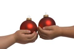 Holding a bulb 2. Two sisters hold red christmas bulbs for the tree Royalty Free Stock Photos