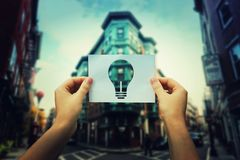 Holding bulb icon. Woman hands holding a paper sheet with bulb icon in the middle of the street in a big city. Finding the ideal place for a business office stock images