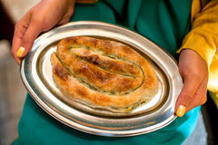 Holding Burek on the metal plate Stock Images