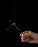 Holding a burning sparkler Royalty Free Stock Images