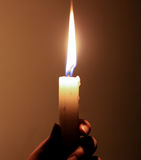 Holding a candle in darkness Royalty Free Stock Image