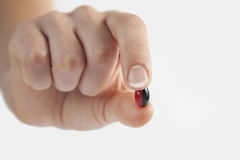 Holding capsule. Woman hand holding black and white pills on white isolated background Royalty Free Stock Image