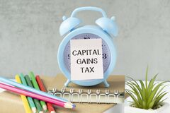 Holding a card with text CAPITAL GAINS TAX on alarm clock , business concept image with soft focus background