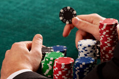 Holding a casino chip. A closeup of a gambler holding a black chip stock images