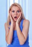 Holding caucasica della donna il suo fronte nella stupefazione Fotografie Stock