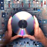Holding a CD above a circuit board. Stock Photos
