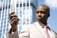 Holding Cell Up. Close up of a businessman using a cell phone in the financial district Royalty Free Stock Photo