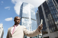 Holding Cell Up. Businessman using a cell phone while standing in the financial district stock photos