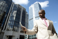 Holding Cell Up. Businessman using a cell phone while standing in the financial district stock photography