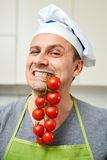 Holding cherry tomatoes in his teeth Stock Photo
