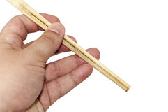 Holding chinese chopsticks in hand over white.  Royalty Free Stock Photo