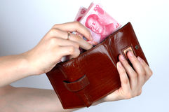 Holding Chinese money and wallet. Hand holding Chinese money, RMB banknotes. Putting money into wallet Stock Image
