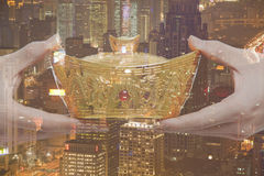 Holding Chinese New Year Gold Ingot, Night City View stock photography