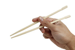 Holding a chopstick. A hand holding a wooden chopstick isolated on white with clipping path royalty free stock photography