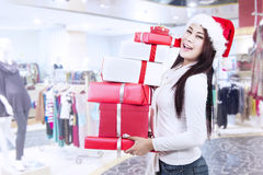 Holding christmas boxes with santa hat at mall Royalty Free Stock Photo