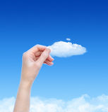 Holding A Cloud Concept. Woman hand hold the cloud against blue sky with clouds. Concept image on cloud computing and eco theme with copy space Stock Photos