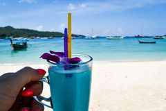 Holding a cocktail at the beach. With boats in the background and enjoying life Royalty Free Stock Images