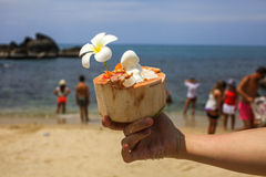 Holding a coconut decorated with orchid flower. Ice cream on summer coconut with orchid flower on the tropical beach with people blurred behind Royalty Free Stock Photos