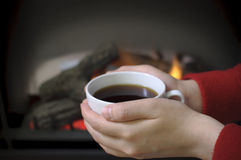 Holding coffee in fornt of fireplace Royalty Free Stock Photos